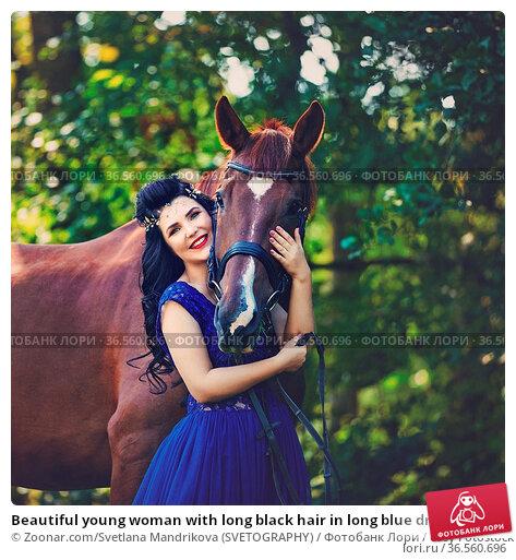 Beautiful young woman with long black hair in long blue dress holding... Стоковое фото, фотограф Zoonar.com/Svetlana Mandrikova (SVETOGRAPHY) / easy Fotostock / Фотобанк Лори