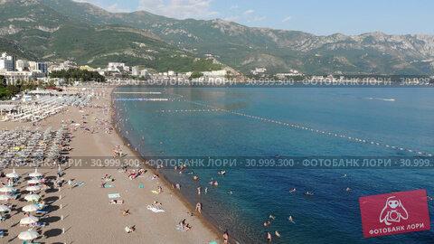 Купить «Becici, Montenegro - June 12.2019. Beautiful top view of the beach with people.», видеоролик № 30999300, снято 17 июля 2019 г. (c) Володина Ольга / Фотобанк Лори