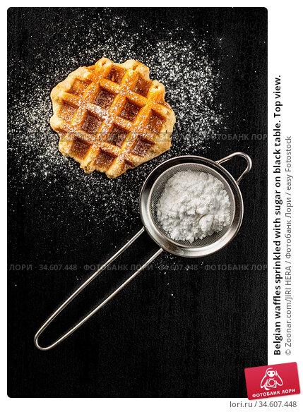 Belgian waffles sprinkled with sugar on black table. Top view. Стоковое фото, фотограф Zoonar.com/JIRI HERA / easy Fotostock / Фотобанк Лори