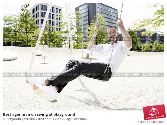Best ager man on swing at playground. Стоковое фото, фотограф Benjamin Egerland / age Fotostock / Фотобанк Лори