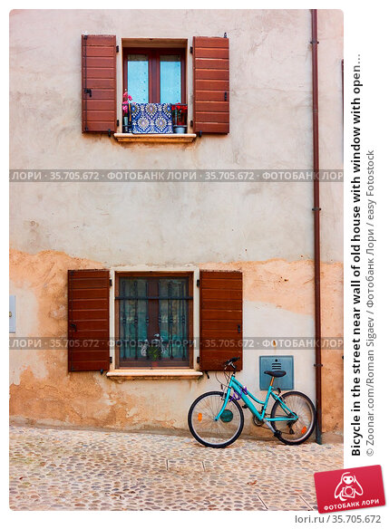 Bicycle in the street near wall of old house with window with open... Стоковое фото, фотограф Zoonar.com/Roman Sigaev / easy Fotostock / Фотобанк Лори