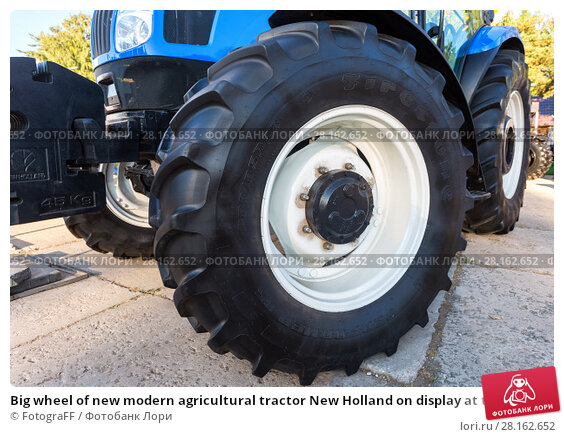 Купить «Big wheel of new modern agricultural tractor New Holland on display at the annual Volga agro-industrial exhibition», фото № 28162652, снято 23 сентября 2017 г. (c) FotograFF / Фотобанк Лори