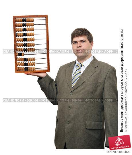 Бизнесмен держит в руке старые деревянные счеты, фото № 309464, снято 1 июня 2008 г. (c) Михаил Коханчиков / Фотобанк Лори