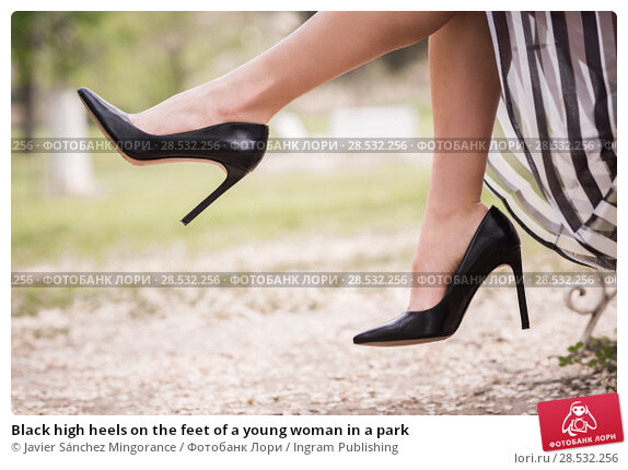 Купить «Black high heels on the feet of a young woman in a park», фото № 28532256, снято 14 апреля 2015 г. (c) Ingram Publishing / Фотобанк Лори