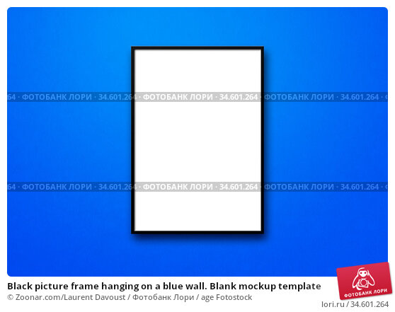 Black picture frame hanging on a blue wall. Blank mockup template. Стоковое фото, фотограф Zoonar.com/Laurent Davoust / age Fotostock / Фотобанк Лори