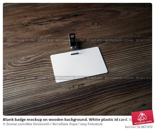 Blank badge mockup on wooden background. White plastic id card. Space for text. Стоковое фото, фотограф Zoonar.com/Alex Veresovich / easy Fotostock / Фотобанк Лори