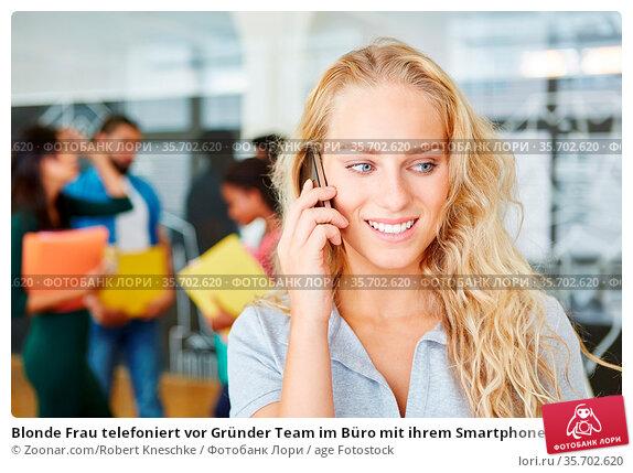 Blonde Frau telefoniert vor Gründer Team im Büro mit ihrem Smartphone. Стоковое фото, фотограф Zoonar.com/Robert Kneschke / age Fotostock / Фотобанк Лори