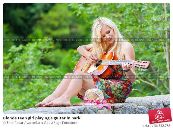 Blonde teen girl playing a guitar in park. Стоковое фото, фотограф Emil Pozar / age Fotostock / Фотобанк Лори