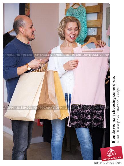 Купить «Blonde woman choosing some dress», фото № 28539208, снято 22 февраля 2016 г. (c) Татьяна Яцевич / Фотобанк Лори