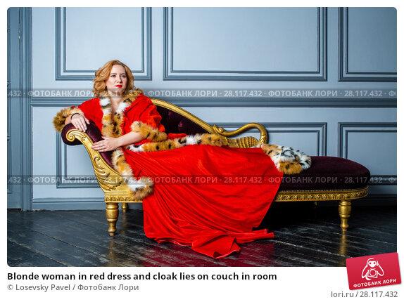 Купить «Blonde woman in red dress and cloak lies on couch in room», фото № 28117432, снято 14 ноября 2015 г. (c) Losevsky Pavel / Фотобанк Лори