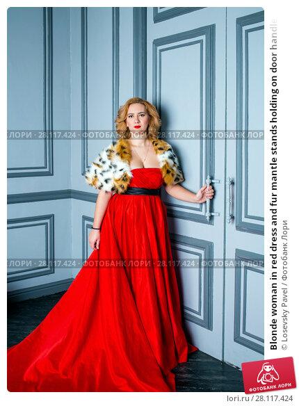 Купить «Blonde woman in red dress and fur mantle stands holding on door handle», фото № 28117424, снято 14 ноября 2015 г. (c) Losevsky Pavel / Фотобанк Лори