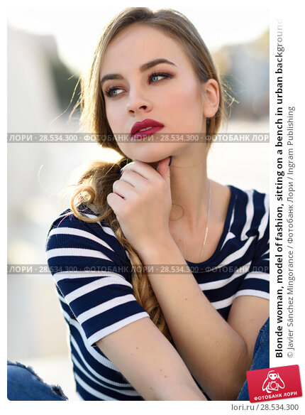 Купить «Blonde woman, model of fashion, sitting on a bench in urban background. Beautiful young girl wearing striped t-shirt and blue jeans in the street. Pretty russian female with pigtail.», фото № 28534300, снято 24 января 2017 г. (c) Ingram Publishing / Фотобанк Лори
