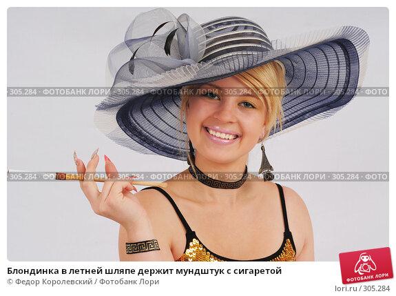Блондинка в летней шляпе держит мундштук с сигаретой, фото № 305284, снято 30 мая 2008 г. (c) Федор Королевский / Фотобанк Лори