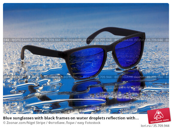 Blue sunglasses with black frames on water droplets reflection with... Стоковое фото, фотограф Zoonar.com/Nigel Stripe / easy Fotostock / Фотобанк Лори