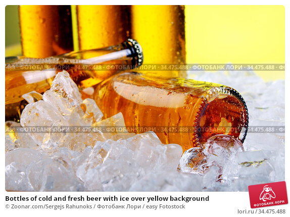 Bottles of cold and fresh beer with ice over yellow background. Стоковое фото, фотограф Zoonar.com/Sergejs Rahunoks / easy Fotostock / Фотобанк Лори