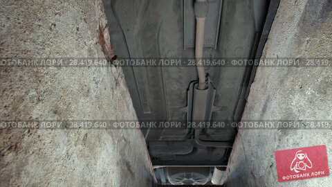 Купить «Bottom of car drives on the inspection pit in garage», видеоролик № 28419640, снято 24 мая 2018 г. (c) Константин Шишкин / Фотобанк Лори