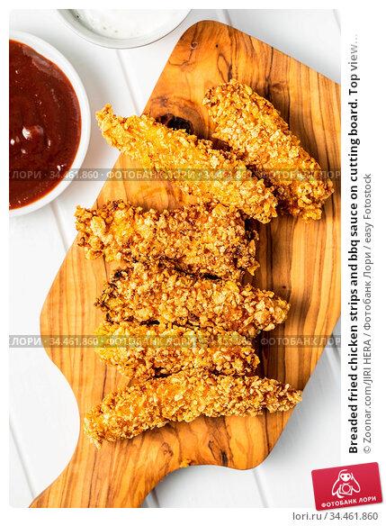 Breaded fried chicken strips and bbq sauce on cutting board. Top view... Стоковое фото, фотограф Zoonar.com/JIRI HERA / easy Fotostock / Фотобанк Лори