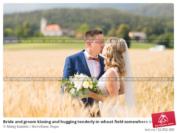 Bride and groom kissing and hugging tenderly in wheat field somewhere in Slovenian countryside. Стоковое фото, фотограф Matej Kastelic / Фотобанк Лори