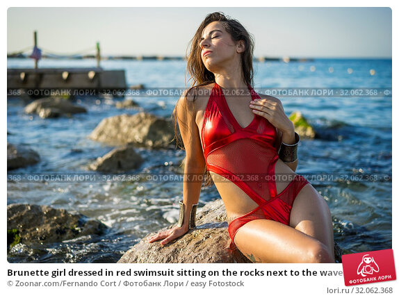Brunette girl dressed in red swimsuit sitting on the rocks next to the waves of the sea. Стоковое фото, фотограф Zoonar.com/Fernando Cort / easy Fotostock / Фотобанк Лори