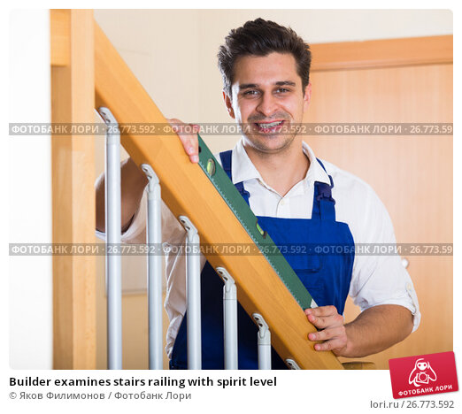Builder examines stairs railing with spirit level, фото № 26773592, снято 22 сентября 2017 г. (c) Яков Филимонов / Фотобанк Лори