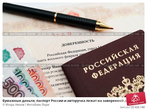 Бумажные деньги, паспорт России и авторучка лежат на заверенной доверенности (2017 год). Редакционное фото, фотограф Игорь Низов / Фотобанк Лори