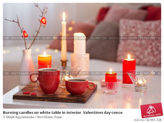 Burning candles on white table in interior. Valentines day conce. Стоковое фото, фотограф Майя Крученкова / Фотобанк Лори
