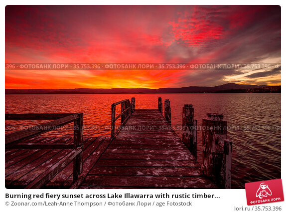 Burning red fiery sunset across Lake Illawarra with rustic timber... Стоковое фото, фотограф Zoonar.com/Leah-Anne Thompson / age Fotostock / Фотобанк Лори