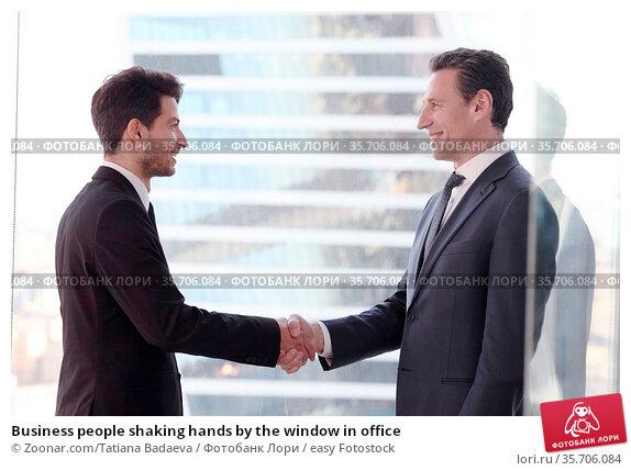 Business people shaking hands by the window in office. Стоковое фото, фотограф Zoonar.com/Tatiana Badaeva / easy Fotostock / Фотобанк Лори