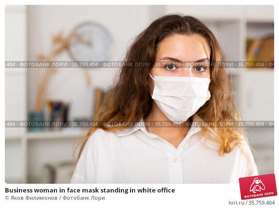 Business woman in face mask standing in white office. Стоковое фото, фотограф Яков Филимонов / Фотобанк Лори