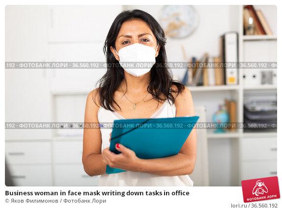 Business woman in face mask writing down tasks in office. Стоковое фото, фотограф Яков Филимонов / Фотобанк Лори