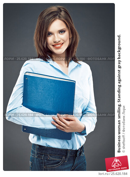 Business woman smiling. Standing against gray background., фото № 25620184, снято 9 апреля 2014 г. (c) sheftsoff / Фотобанк Лори