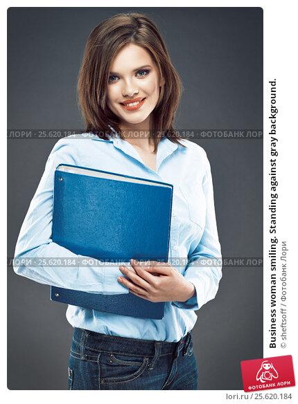 Business woman smiling. Standing against gray background., фото № 25620184, снято 9 апреля 2014 г. (c) sheftsoff / Фотобанк Лори