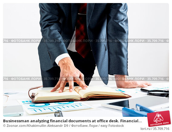 Businessman analyzing financial documents at office desk. Financial... Стоковое фото, фотограф Zoonar.com/Khakimullin Aleksandr D9 / easy Fotostock / Фотобанк Лори
