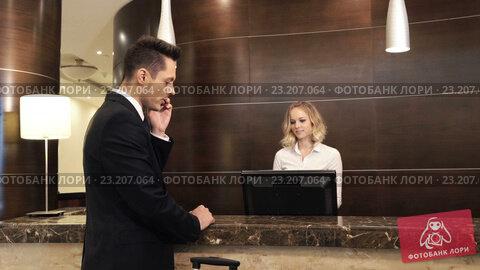 Купить «Businessman at reception in a hotel», видеоролик № 23207064, снято 30 июня 2016 г. (c) Raev Denis / Фотобанк Лори