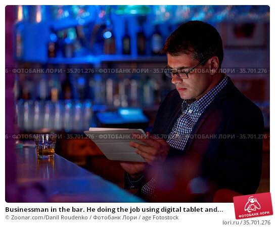 Businessman in the bar. He doing the job using digital tablet and... Стоковое фото, фотограф Zoonar.com/Danil Roudenko / age Fotostock / Фотобанк Лори