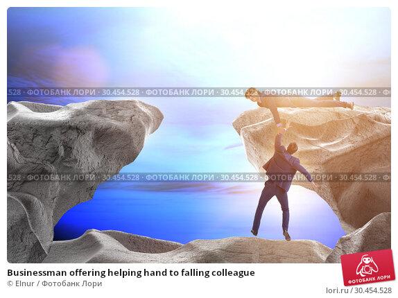 Businessman offering helping hand to falling colleague. Стоковое фото, фотограф Elnur / Фотобанк Лори