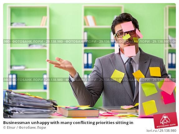 Купить «Businessman unhappy with many conflicting priorities sitting in», фото № 29138980, снято 18 мая 2018 г. (c) Elnur / Фотобанк Лори