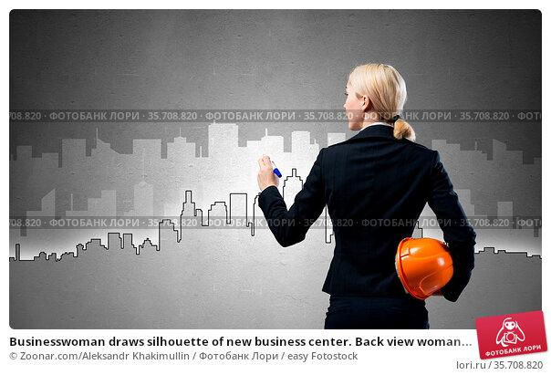 Businesswoman draws silhouette of new business center. Back view woman... Стоковое фото, фотограф Zoonar.com/Aleksandr Khakimullin / easy Fotostock / Фотобанк Лори