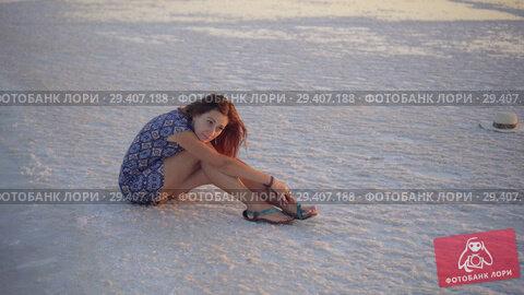 Купить «Calm girl enjoying sun, sits on the ground covered with salt close to lake», видеоролик № 29407188, снято 3 ноября 2018 г. (c) Ирина Мойсеева / Фотобанк Лори