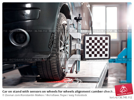 Car on stand with sensors on wheels for wheels alignment camber check... Стоковое фото, фотограф Zoonar.com/Konstantin Malkov / easy Fotostock / Фотобанк Лори