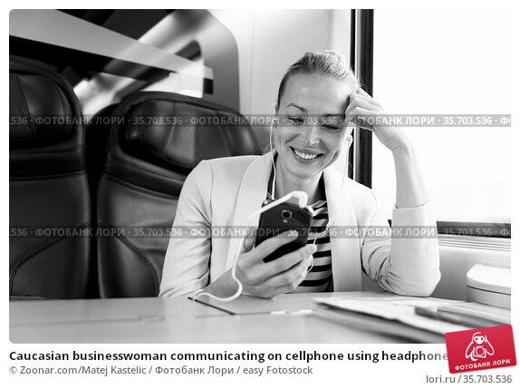 Caucasian businesswoman communicating on cellphone using headphone... Стоковое фото, фотограф Zoonar.com/Matej Kastelic / easy Fotostock / Фотобанк Лори