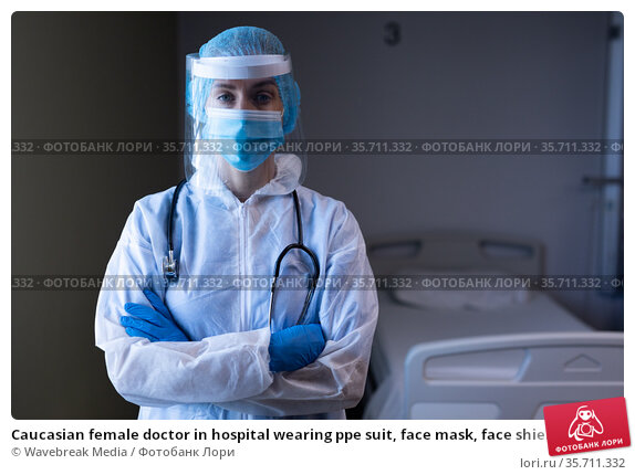 Caucasian female doctor in hospital wearing ppe suit, face mask, face shield and medical cap. Стоковое фото, агентство Wavebreak Media / Фотобанк Лори