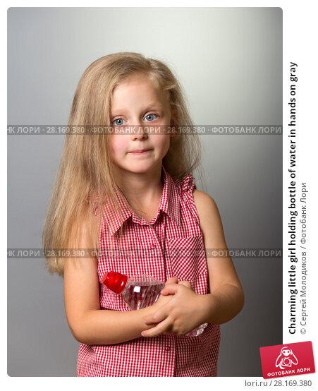 Купить «Charming little girl holding bottle of water in hands on gray», фото № 28169380, снято 23 сентября 2017 г. (c) Сергей Молодиков / Фотобанк Лори