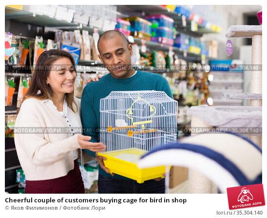 Cheerful couple of customers buying cage for bird in shop. Стоковое фото, фотограф Яков Филимонов / Фотобанк Лори