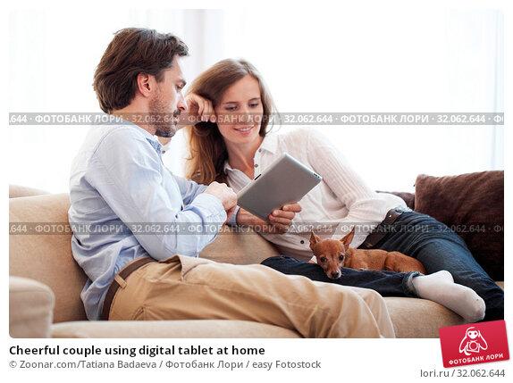 Cheerful couple using digital tablet at home. Стоковое фото, фотограф Zoonar.com/Tatiana Badaeva / easy Fotostock / Фотобанк Лори