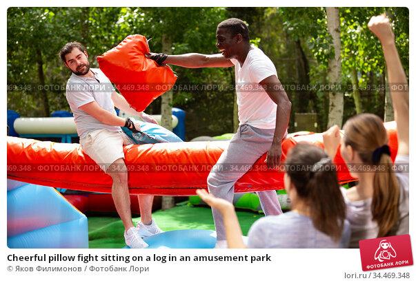Cheerful pillow fight sitting on a log in an amusement park. Стоковое фото, фотограф Яков Филимонов / Фотобанк Лори