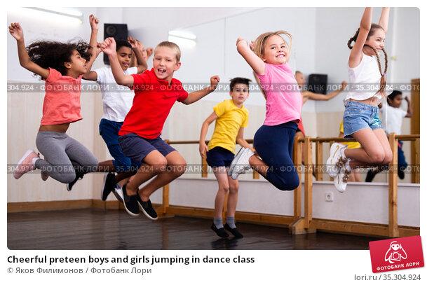 Cheerful preteen boys and girls jumping in dance class. Стоковое фото, фотограф Яков Филимонов / Фотобанк Лори