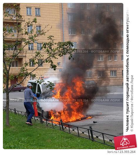 Человек тушит горящий автомобиль с помощью огнетушителя (2016 год). Редакционное фото, фотограф Юрий Пирогов / Фотобанк Лори