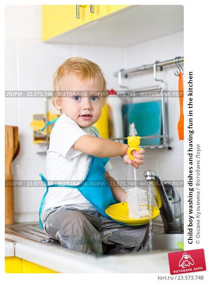 Купить «Child boy washing dishes and having fun in the kitchen», фото № 23573748, снято 13 октября 2015 г. (c) Оксана Кузьмина / Фотобанк Лори