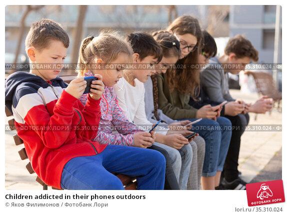 Children addicted in their phones outdoors. Стоковое фото, фотограф Яков Филимонов / Фотобанк Лори